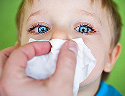 Child wiping the nose with tissue