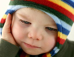 Image of a child wearing a colourful bonnet