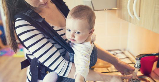 Mother carrying her baby in a baby carrier while dishwashing