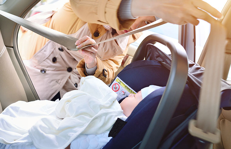Mother adjusting the safety straps in the baby car seat.