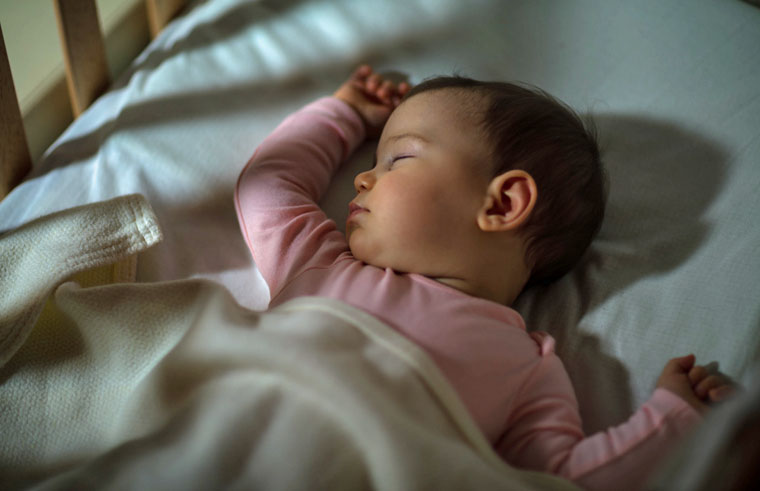A baby sleeping in a cot